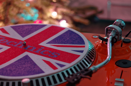 Retro vinyl record player in the front of a Christmas tree as a gift for Christmas