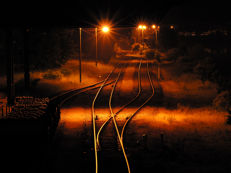 Empty freight yard with parked wagon and orange street lights at night