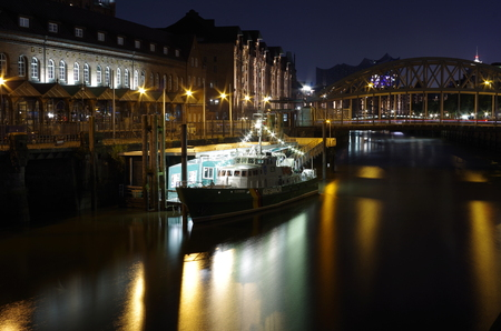 Hamburg customs canal with historic customs boat and bridge in the background at night Stock Photo