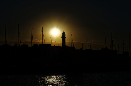 Sunset in the harbor of Warnemünde on the Baltic sea in Germany with lighthouse and sailing yachts