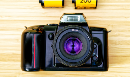 Analog black reflex camera on a bamboo table with two analogue films in the background