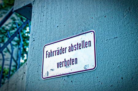 Sign and prohibition sign with the warning in german. Stop bicycles prohibited in english parking Bikes is not allowed