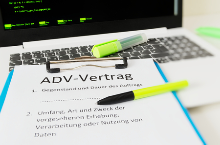 Clipboard with a contract and inscription in german ADV-Vertrag in english ADV contract and subject matter and duration of the contract and scope type and purpose of the proposed survey