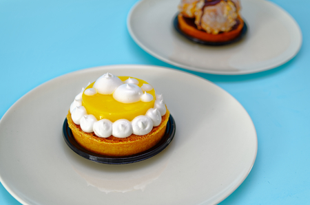 Two cake particles with lemon and chocolate on two white plates by a pastry chef with light blue background Stock Photo
