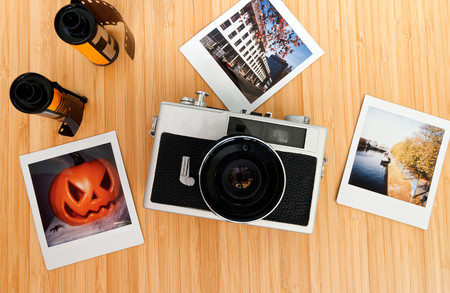Instant camera in white with exposed instant films and drotty headphones on a bamboo table