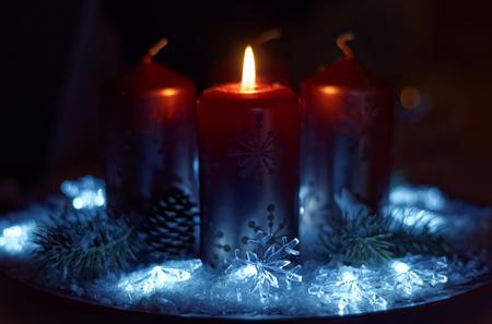 Adventskranz in rotgoldenen Kerzen mit Schnee als Hintergrund und noch nicht angezündeten Kerzen