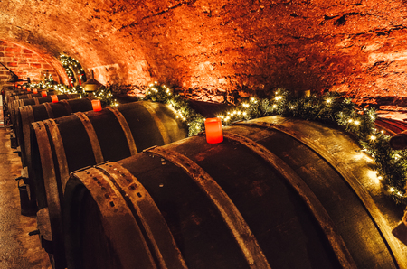 Wine barrels in an old wine cellar with red candles and fairy lights