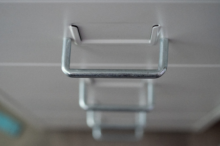 Drawer of a metal cupboard in white with metal grips