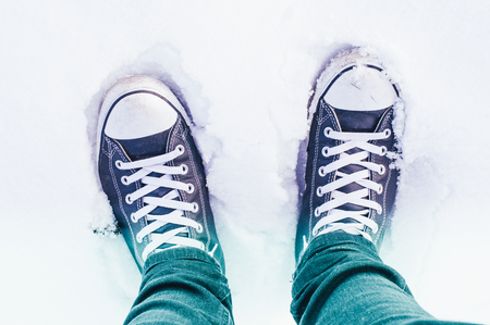 Sneaker in the snow with leather and jeans Banque d'images