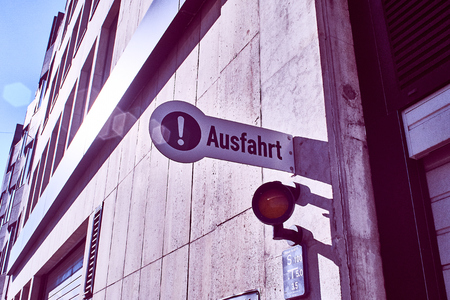 Garage of an office building with holding the sign and gate with gate and sign in german Ausfahrt in english exit Standard-Bild - 124811670