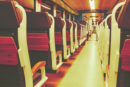 Train seats in a train compartment in white optic with wood at a train station at night Standard-Bild - 124811680
