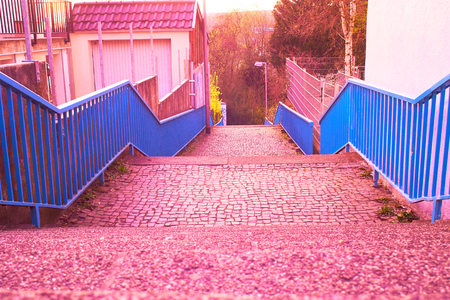 Footpath with stairs and blue railing at dusk with filter in purple Standard-Bild - 124811683