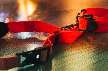 Camera strap in orange with a loop on a parquet floor