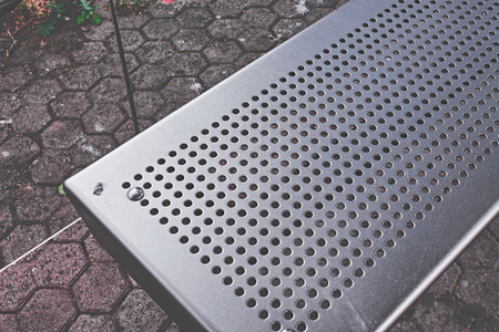 Bench of a bus stop with steel sheet and holes
