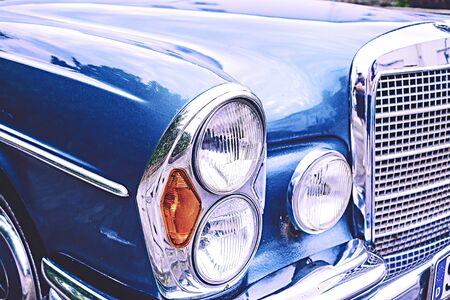 Vieille voiture vintage en bleu avec calandre et lampes avec beaucoup de chrome