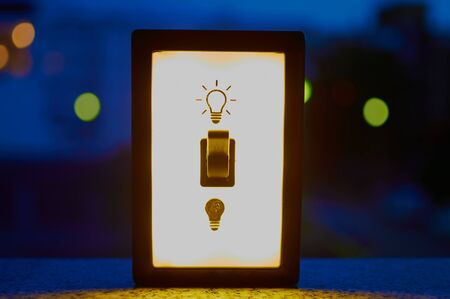 Light switch against a nocturnal background in a city to illustrate the environmental pollution by power generation Banco de Imagens