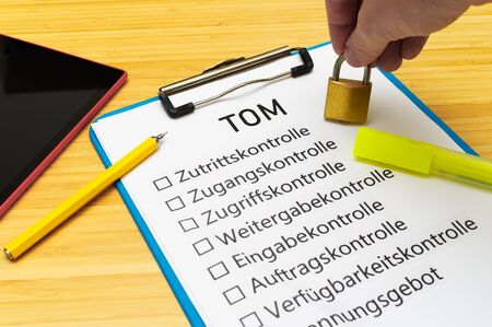 Plate with the inscription TOM (Technisch organisatorische Maßnahmen)  in English Technically organizational measures with a tablet and block to signal typical activities of data protection officers Standard-Bild