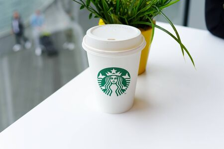Starbucks Coffee-To-Go Mug with banderole on a white table to illustrate plastic waste in a Starbucks restaurant in Koblenz photographed on 2019.08.17 Standard-Bild - 137812212