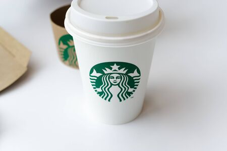 Starbucks Coffee-To-Go Mug with banderole on a white table to illustrate plastic waste in a Starbucks restaurant in Koblenz photographed on 2019.08.17 Standard-Bild - 137812213