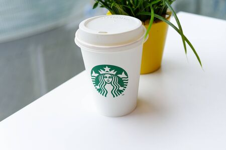 Starbucks Coffee-To-Go Mug with banderole on a white table to illustrate plastic waste in a Starbucks restaurant in Koblenz photographed on 2019.08.17 Standard-Bild - 137812244