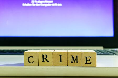 Letters with the words CRIME in front of a laptop that is currently updating Standard-Bild - 139189328