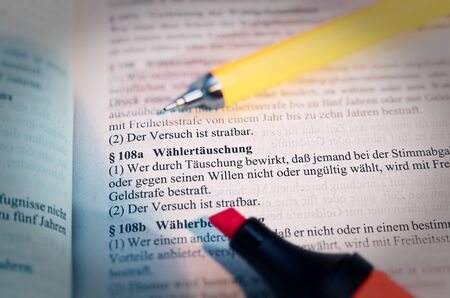 Legal text with § 108a StGB German law Wählertäuschung in English Voter deception with pen and highlighter 免版税图像