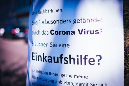 Sign on a tree that offers help for the elderly in the Corona crisis in German Einkaufshilfe für ältere Menschen die besonders gefährdet sind in English Shopping aid for older people who are particularly at risk