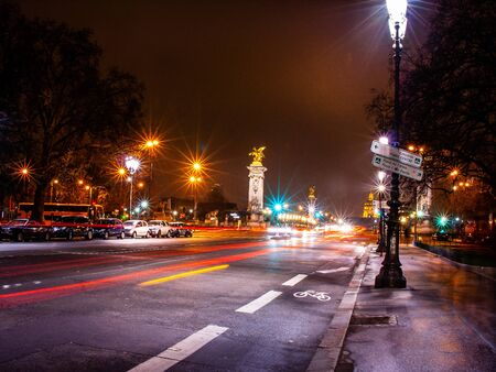 Champs-Elysees in Paris at night with headlights and cars