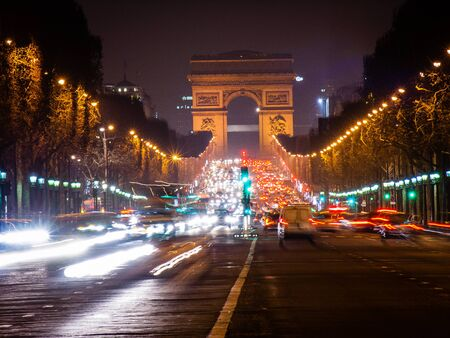 Arc de Triomphe and Champs-Elysees Trump Arch in Paris at night with headlights and cars