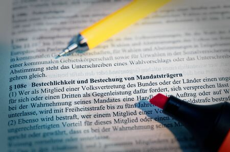 Legal text with ? 108e StGB in German Bribery and bribery of mandate holders with pen and highlighter in English Bribery and bribery of mandate holders