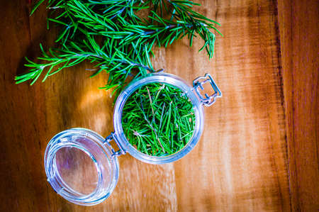 Dried rosemary as a spice in a glass on a rustic wooden table Standard-Bild - 155574080