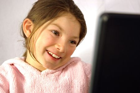 Smiling, young girl at laptop computer