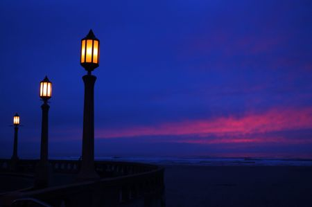 Lamps, along the beach at the Oregon coast, flicker to life as the sun sets. Imagens
