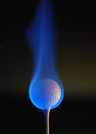 Golfball engulfed in blue flames. Lighting from the right hand side.