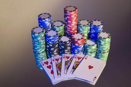 jack pot: Royal Flush, hearts, with poker chips, left hand blue lighting on mirror.