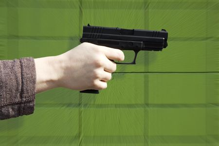 Hand holding pistol, green wall background Stock Photo