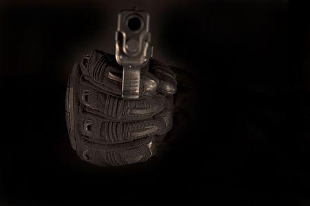黒手袋をはめた手ピストルを。グローブに焦点を当てます。 写真素材