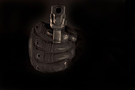 Black gloved hand with pistol. Focus on glove. 스톡 콘텐츠