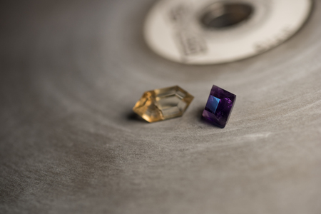 Amethyst and sunstone on a faceting lap with shallow depth-of-field.