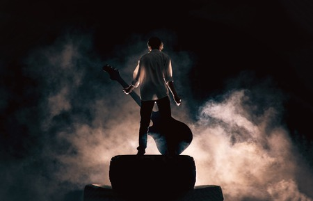 The musician plays on a large rock guitar in a great smoke Stock fotó - 43080924
