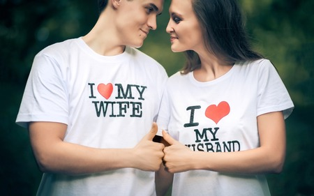 Young husband and wife with the words on the T-shirt I love my wife, I love my husband Stok Fotoğraf