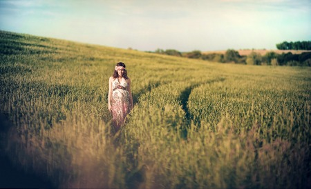 Romantic pregnant woman outside in the field and greenery like fairytale