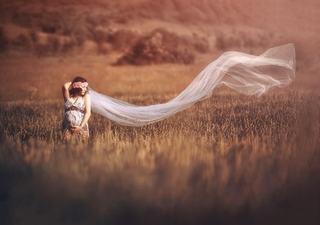 Romantic and beautiful pregnant woman outside in the field like a fairytale Stok Fotoğraf