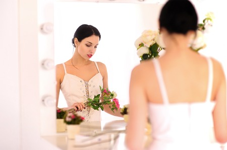 Beautiful young ballerina standing against mirror and looking at her flowers. Stok Fotoğraf