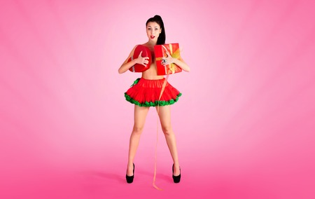 Joyful naked girl in red skirt, having fun emotionally enjoying is covered with gift boxes on red background in Valentine day.