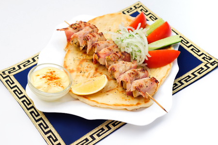 Souvlaki, kebab, grilled meat on pita bread with sauce, tomatoes and cucumbers, white plate Stok Fotoğraf