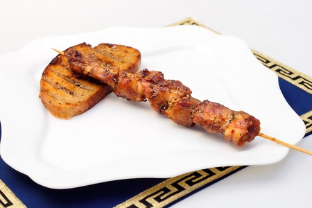 Souvlaki or kebab, grilled meat with grilled bread, white plate