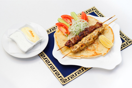 Souvlaki or kebab, grilled meat on pita bread with tomatoes and cucumbers on white plate Stok Fotoğraf