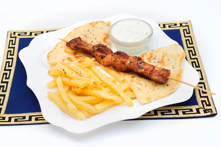 Souvlaki or kebab, grilled meat on pita bread with sauce and french fries, white plate