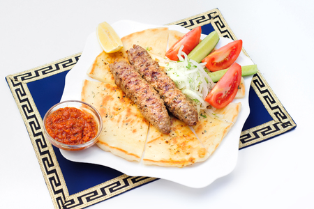 Souvlaki, kebab, grilled meat on pita bread with tomatoes and cucumbers on white plate